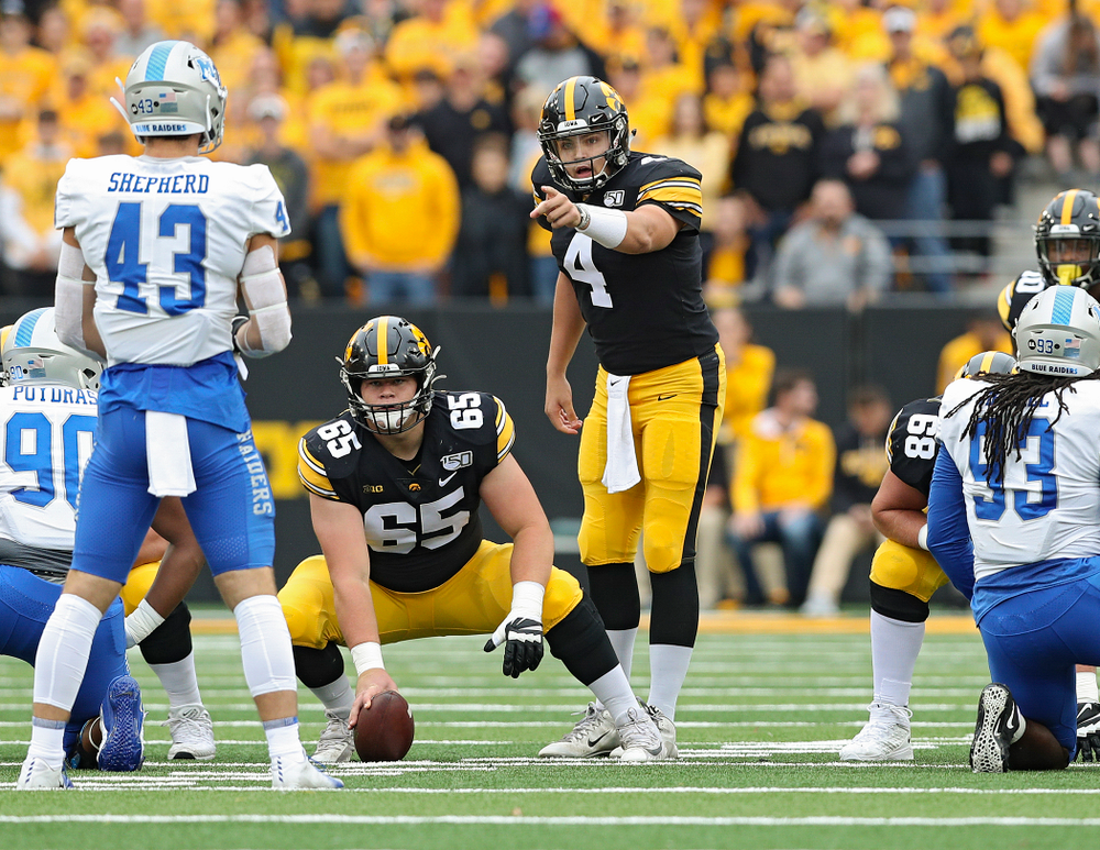 Iowa Hawkeyes quarterback Nate Stanley (4) points across the line as offensive lineman Tyler Linderbaum (65) looks on during the first quarter of their game at Kinnick Stadium in Iowa City on Saturday, Sep 28, 2019. (Stephen Mally/hawkeyesports.com)