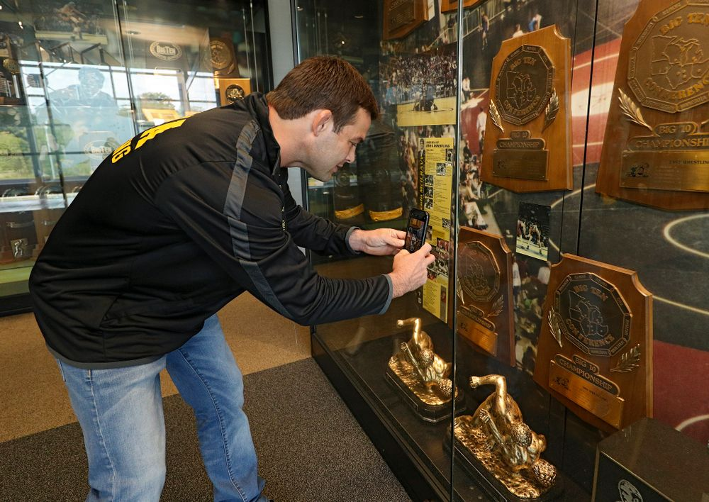 2019 University of Iowa Athletics Hall of Fame inductee Eric Juergens takes a picture of a photo of himself in the wrestling display at the University of Iowa Athletics Hall of Fame in Iowa City on Friday, Aug 30, 2019. (Stephen Mally/hawkeyesports.com)