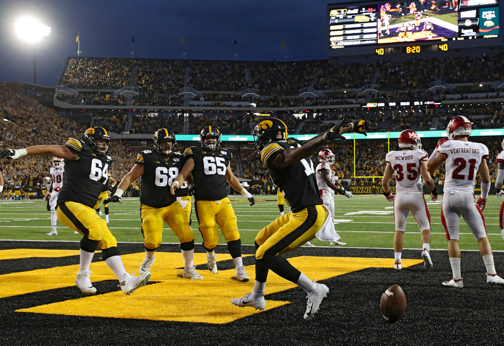 Iowa Hawkeyes offensive lineman Kyler Schott (64), offensive lineman Landan Paulsen (68), and offensive lineman Tyler Linderbaum (65) celebrate with wide receiver Brandon Smith (12) after his 9-yard touchdown reception during the second quarter of their game at Kinnick Stadium in Iowa City on Saturday, Aug 31, 2019. (Stephen Mally/hawkeyesports.com)
