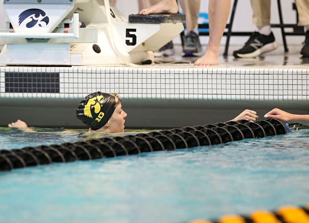 Iowa's Macy Rink (from left) gets a fist bump from Penn State's Camryn Barry after swimming the women's 500 yard freestyle preliminary event during the 2020 Women's Big Ten Swimming and Diving Championships at the Campus Recreation and Wellness Center in Iowa City on Thursday, February 20, 2020. (Stephen Mally/hawkeyesports.com)