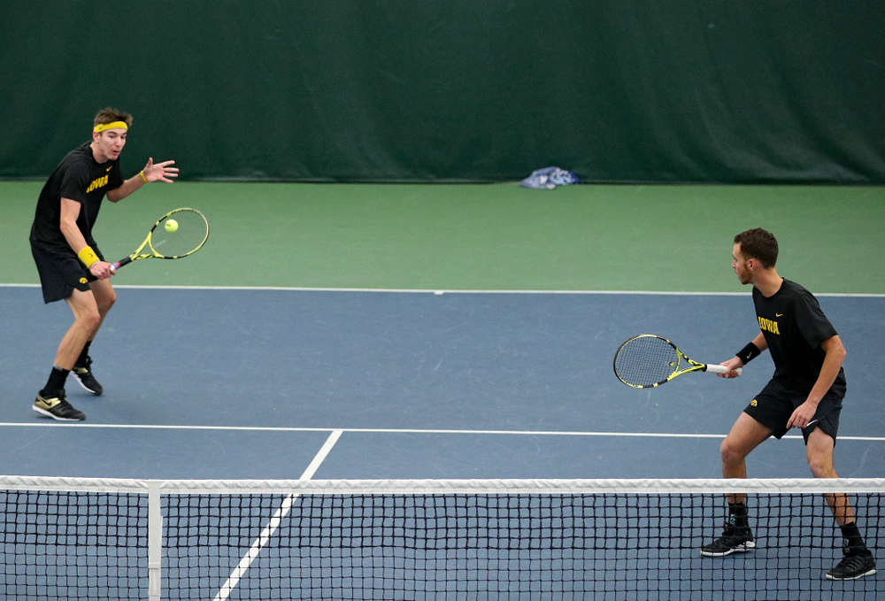 Iowa's Nikita Snezhko (from left) hits a shot as Kareem Allaf looks on during their doubles match against Marquette at the Hawkeye Tennis and Recreation Complex in Iowa City on Saturday, January 25, 2020. (Stephen Mally/hawkeyesports.com)