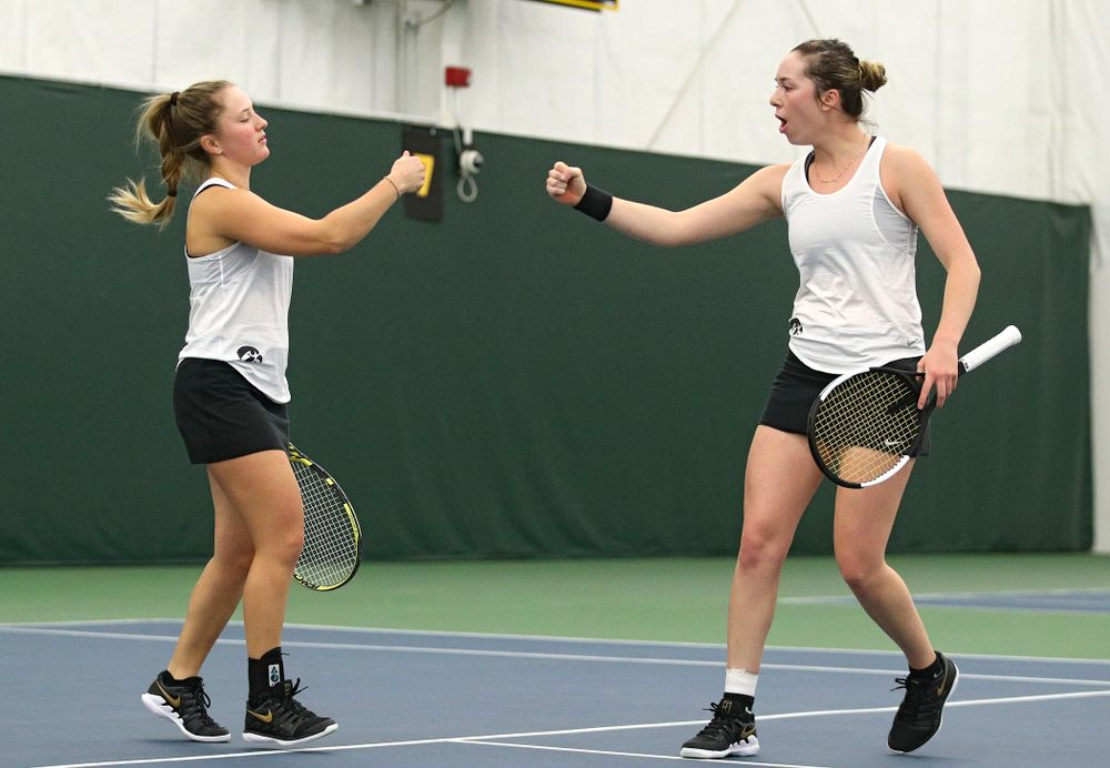 Iowa's Danielle Burich (from left) and Samantha Mannix celebrate a point during her doubles match at the Hawkeye Tennis and Recreation Complex in Iowa City on Sunday, February 23, 2020. (Stephen Mally/hawkeyesports.com)