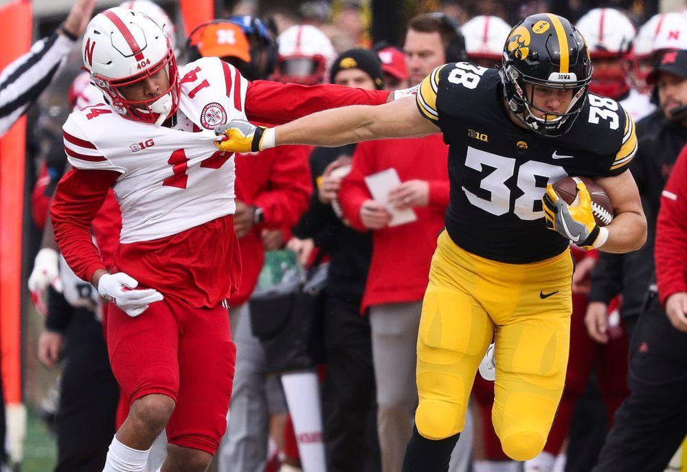 Iowa Hawkeyes tight end T.J. Hockenson (38) stiff-arms a defender