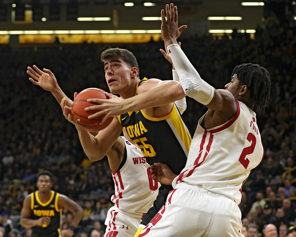 Iowa Hawkeyes center Luka Garza (55) splits two defenders during the first half of their game at Carver-Hawkeye Arena in Iowa City on Monday, January 27, 2020. (Stephen Mally/hawkeyesports.com)