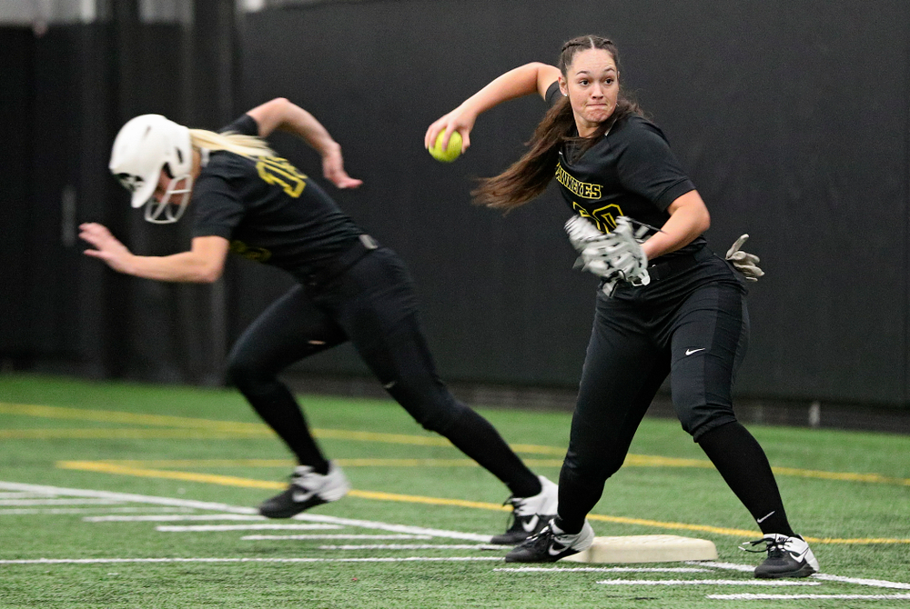 Iowa infielder Kalena Burns (right) throws home while infielder Erin Carter (15) runs to second base as they run a drill during Iowa Softball Media Day at the Hawkeye Tennis and Recreation Complex in Iowa City on Thursday, January 30, 2020. (Stephen Mally/hawkeyesports.com)