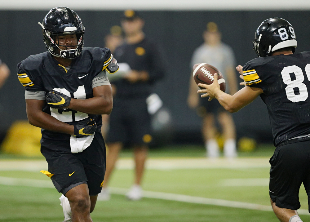 Iowa Hawkeyes running back Ivory Kelly-Martin (21) flips the ball to wide receiver Nico Ragaini (89) during Fall Camp Practice No. 9 at the Hansen Football Performance Center in Iowa City on Monday, Aug 12, 2019. (Stephen Mally/hawkeyesports.com)