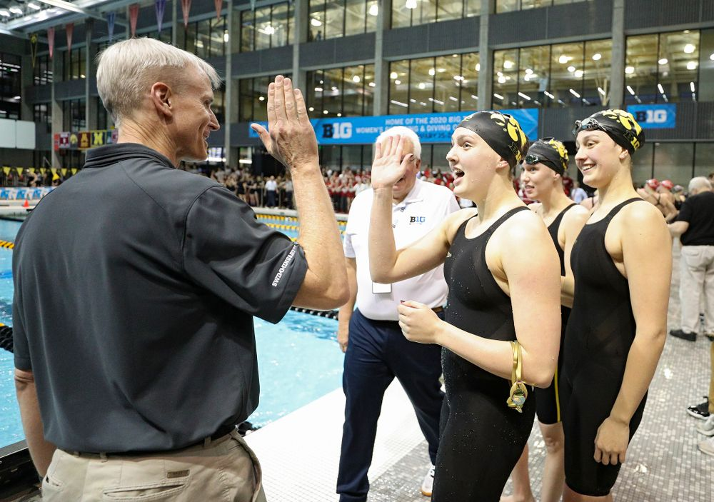 Iowa head coach Marc Long greets Hannah Burvill, Allyssa Fluit, and Emilia Sansome after they placed fourth in the 800 yard freestyle relay event during the 2020 Big Ten Women's Swimming and Diving Championships at the Campus Recreation and Wellness Center in Iowa City on Wednesday, February 19, 2020. (Stephen Mally/hawkeyesports.com)