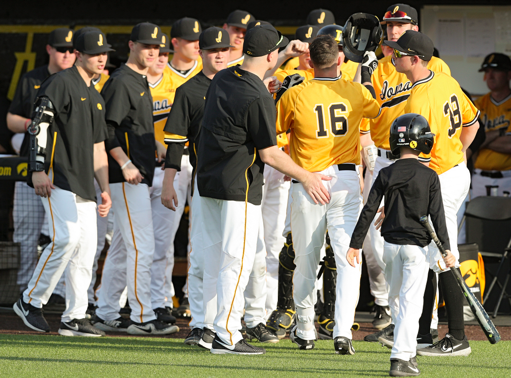 Iowa Hawkeyes shortstop Tanner Wetrich (16) is greeted by teammates after hitting a home run during the fifth inning of their game against Northern Illinois at Duane Banks Field in Iowa City on Tuesday, Apr. 16, 2019. (Stephen Mally/hawkeyesports.com)