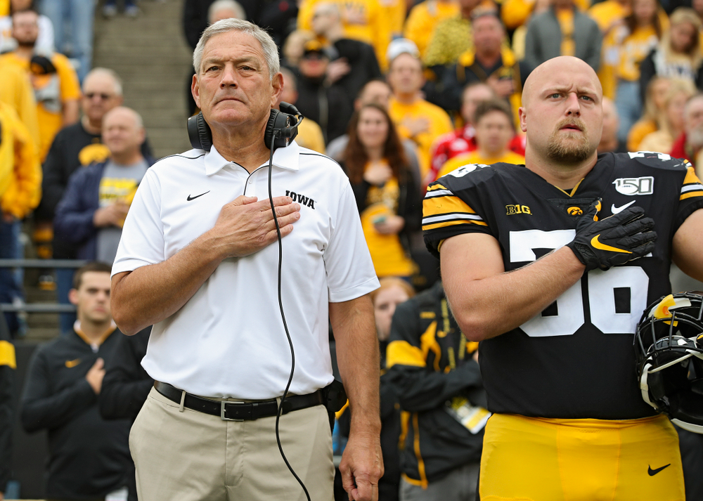 Iowa Hawkeyes head coach Kirk Ferentz (from left) and fullback Brady Ross (36) stand for the National Anthem before their game at Kinnick Stadium in Iowa City on Saturday, Sep 28, 2019. (Stephen Mally/hawkeyesports.com)