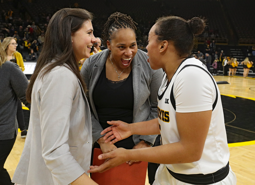Iowa director of player development Kathryn Reynolds (from left), assistant coach Raina Harmon, and guard Alexis Sevillian (5) talk after their overtime win against Princeton at Carver-Hawkeye Arena in Iowa City on Wednesday, Nov 20, 2019. (Stephen Mally/hawkeyesports.com)