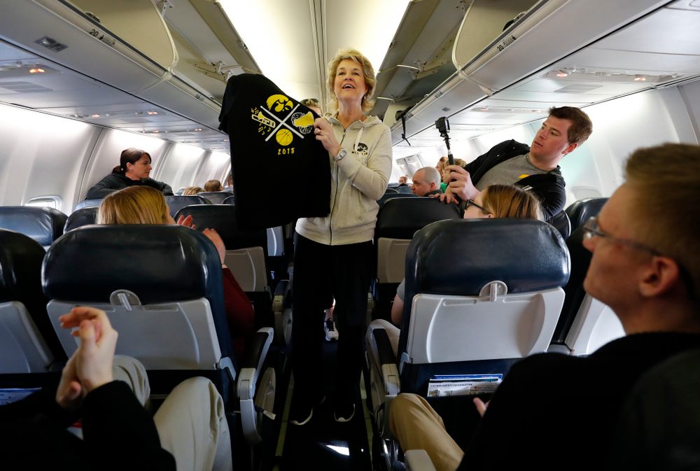 Iowa Hawkeyes head coach Lisa Bluder  hands out t-shirts to the pep band and spirit squad to thank them as they travel to Los Angeles for the first round of the 2018 NCAA Tournament Thursday, March 15, 2018 at the Eastern Iowa Airport. (Brian Ray/hawkeyesports.com)