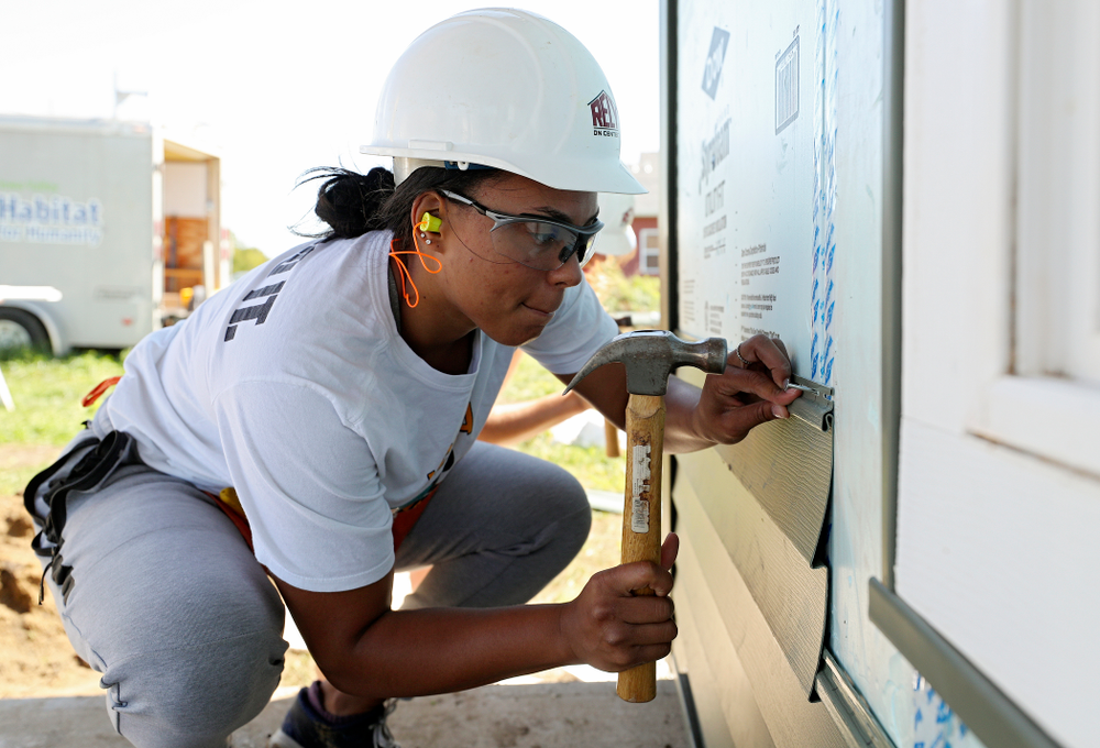 Iowa's Alexis Sevillian hammers in a nail on a piece of siding as they work on a Habitat for Humanity Women Build project in Iowa City on Wednesday, Sep 25, 2019. (Stephen Mally/hawkeyesports.com)