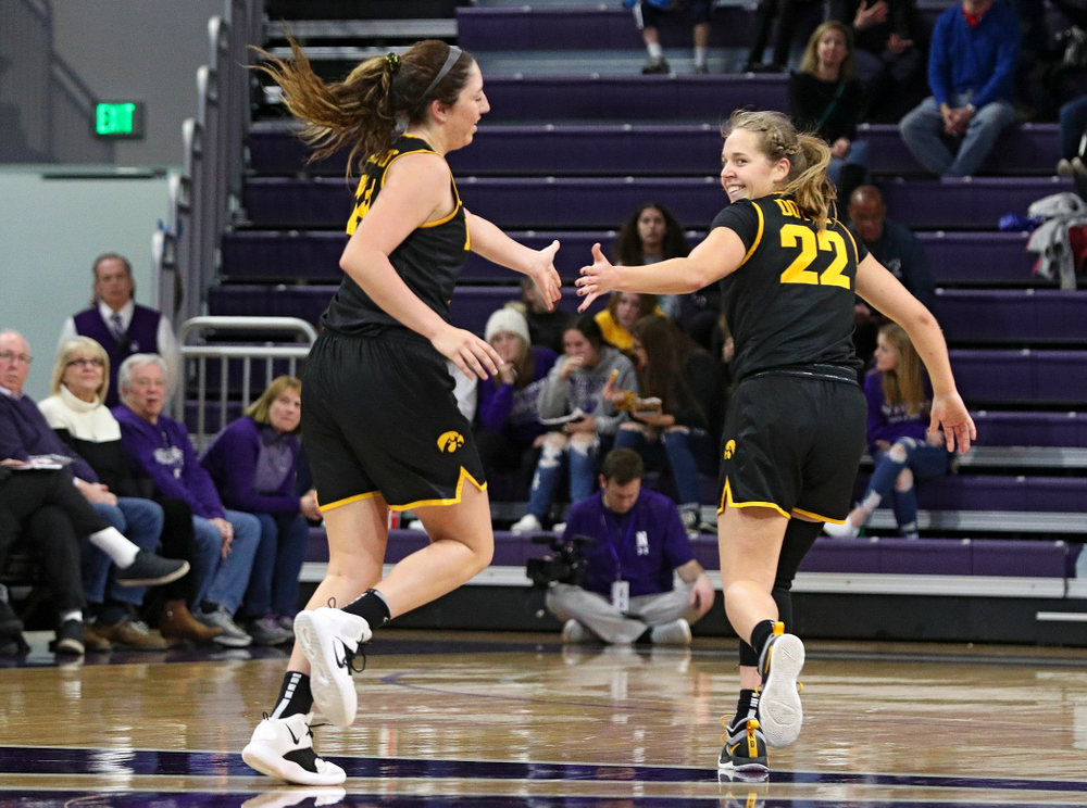 Iowa Hawkeyes guard Mckenna Warnock (14) gets a high-five from guard Kathleen Doyle (22) after Warnock made a 3-pointer during the third quarter of their game at Welsh-Ryan Arena in Evanston, Ill. on Sunday, January 5, 2020. (Stephen Mally/hawkeyesports.com)