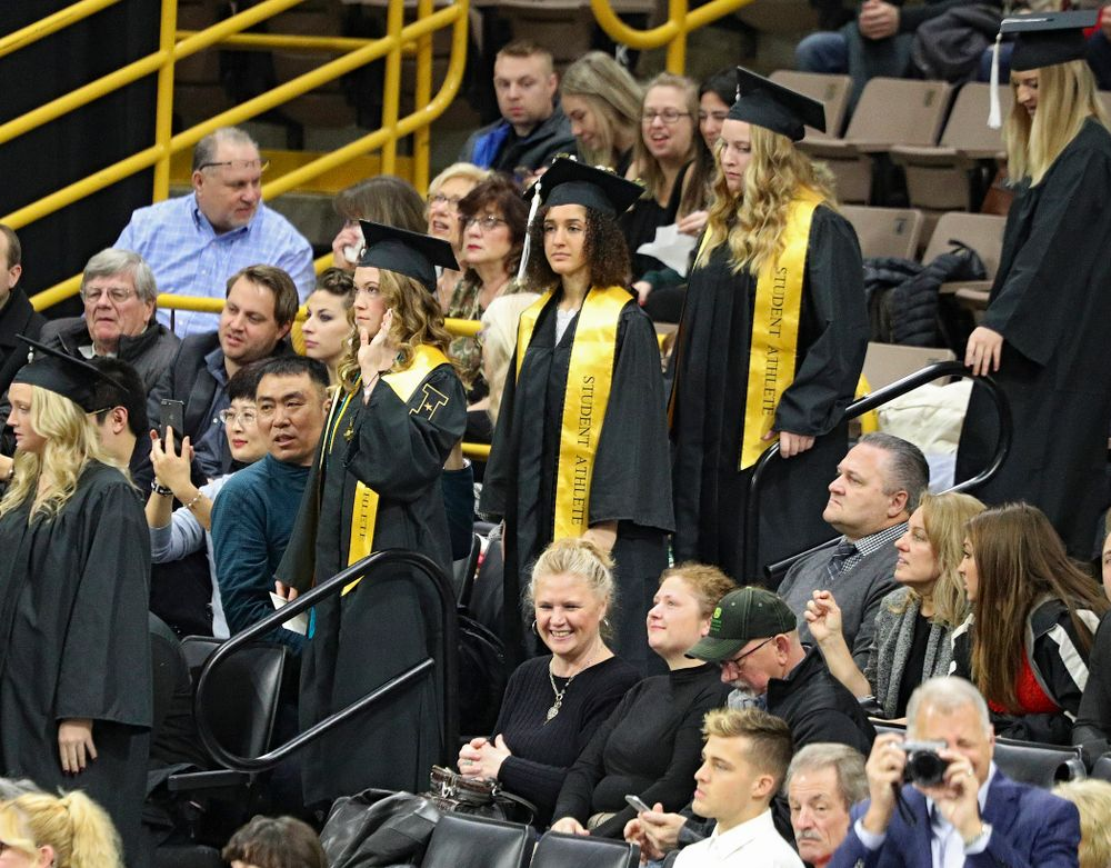 Iowa track and field's Lindsay Welker (from left), Tia Saunders, and Allison Wahrman walk down the steps during the procession in the College of Liberal Arts and Sciences and University College Fall 2019 Commencement ceremony at Carver-Hawkeye Arena in Iowa City on Saturday, December 21, 2019. (Stephen Mally/hawkeyesports.com)