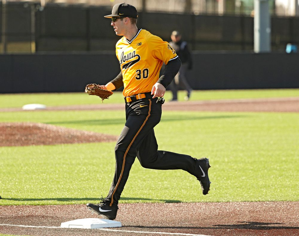 Iowa Hawkeyes first baseman Connor McCaffery (30) steps on first base for an out after fielding a ground ball during the first inning of their game at Duane Banks Field in Iowa City on Tuesday, Apr. 2, 2019. (Stephen Mally/hawkeyesports.com)