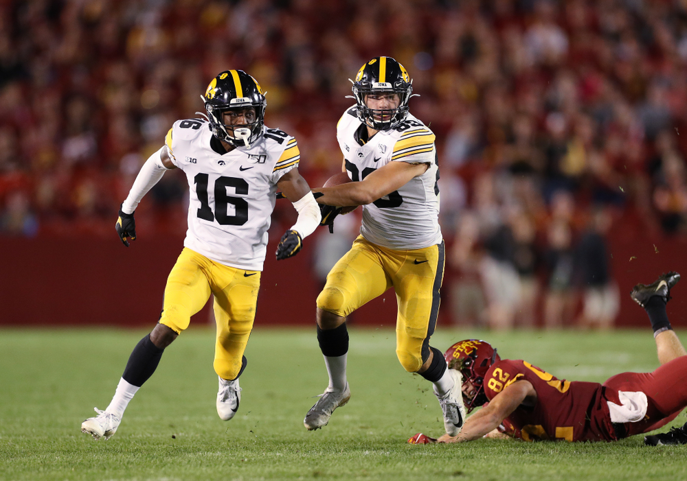 Iowa Hawkeyes wide receiver Nico Ragaini (89) runs behind defensive back Terry Roberts (16)  as he returns a punt against the Iowa State Cyclones Saturday, September 14, 2019 in Ames, Iowa. (Brian Ray/hawkeyesports.com)