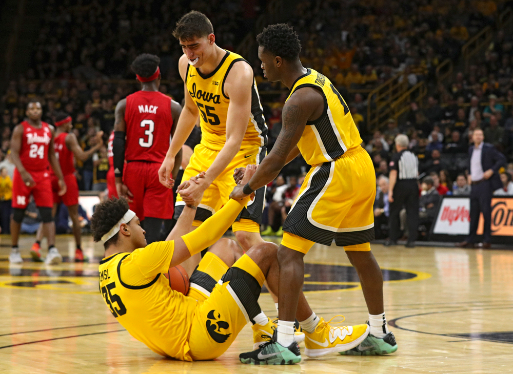 Iowa Hawkeyes center Luka Garza (55) and guard Joe Toussaint (1) help up forward Cordell Pemsl (35) after he was fouled during the first half of their game at Carver-Hawkeye Arena in Iowa City on Saturday, February 8, 2020. (Stephen Mally/hawkeyesports.com)