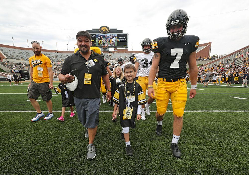 Kid Captain Jackson Tijerina swarms with Iowa Hawkeyes punter Colten Rastetter (7) during Kids Day at Kinnick Stadium in Iowa City on Saturday, Aug 10, 2019. (Stephen Mally/hawkeyesports.com)