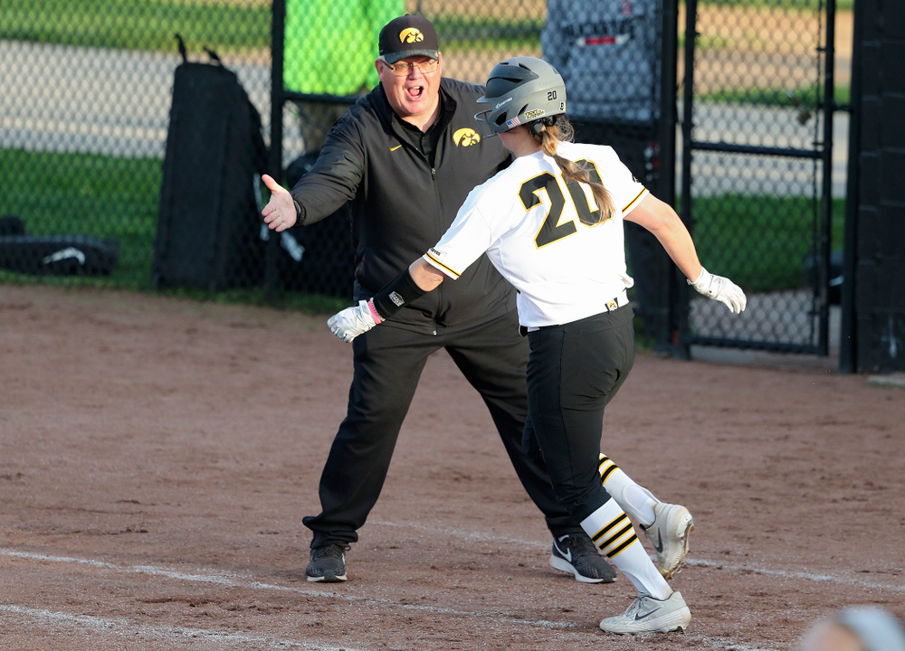 Iowa designated player Miranda Schulte (20) gets a high-five from assistant coach Rick Dillinger after hitting a home run during the sixth inning of their game against Ohio State at Pearl Field in Iowa City on Friday, May. 3, 2019. (Stephen Mally/hawkeyesports.com)