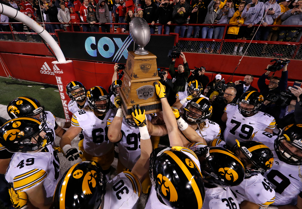 The Iowa Hawkeyes celebrate with the Heroes Game Trophy