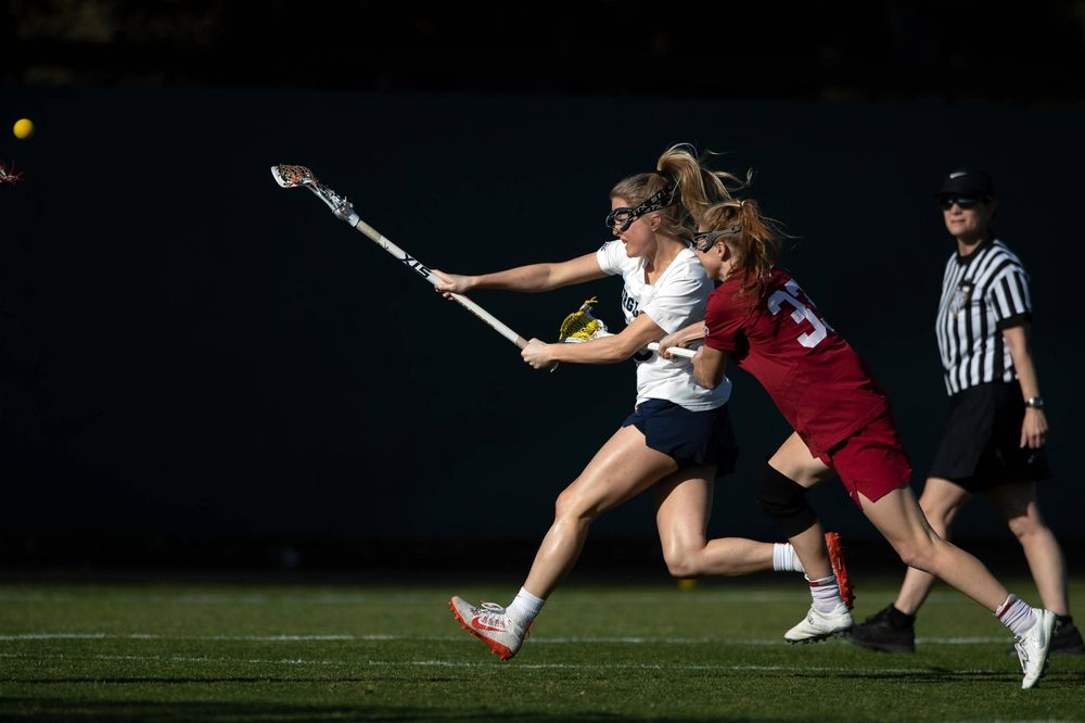 STANFORD, California - FEBRUARY 14:  Virginia Cavaliers midfield Courtlynne Caskin (25) scores a goal past Stanford Cardinal midfield Jacie Lemos (33) during the first half at Cagan Stadium on February 14, 2020 in Stanford, California. The Virginia Cavaliers defeated the Stanford Cardinal 12-11. (Photo by Jason O. Watson)