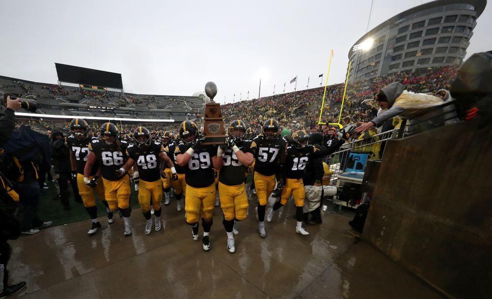 Iowa Hawkeyes offensive lineman Keegan Render (69) and offensive lineman Ross Reynolds (59) carry the Heroes game trophy off the field following their win over the Nebraska Cornhuskers Friday, November 23, 2018 at Kinnick Stadium. (Brian Ray/hawkeyesports.com)