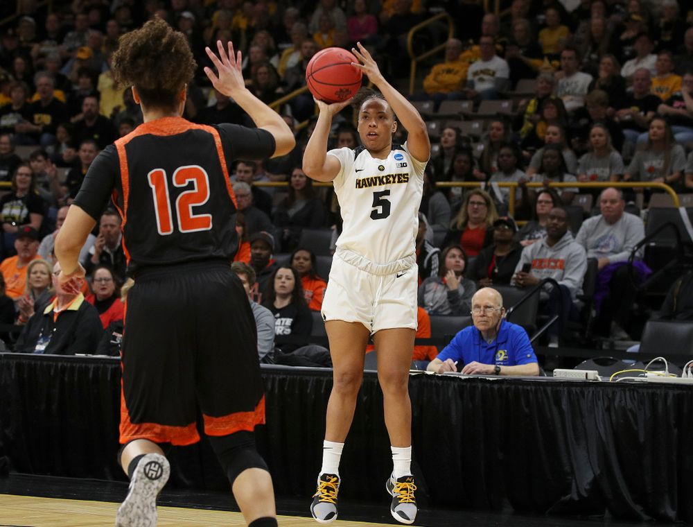 Iowa Hawkeyes guard Alexis Sevillian (5) shoots over Mercer Bears guard Tia Benvenuti (12) during the first round of the 2019 NCAA Women's Basketball Tournament at Carver Hawkeye Arena in Iowa City on Friday, Mar. 22, 2019. (Stephen Mally for hawkeyesports.com)