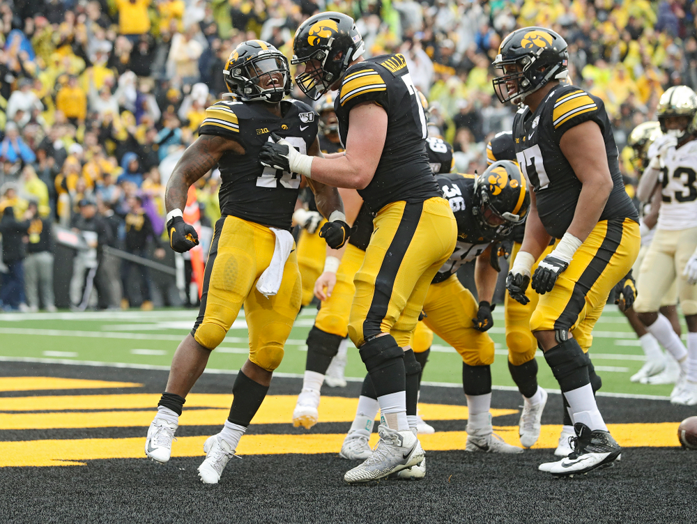 Iowa Hawkeyes running back Mekhi Sargent (10) celebrates his touchdown run with offensive lineman Mark Kallenberger (71) during the fourth quarter of their game at Kinnick Stadium in Iowa City on Saturday, Oct 19, 2019. (Stephen Mally/hawkeyesports.com)