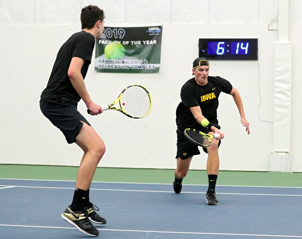 Iowa's Joe Tyler (right) returns a shot as Matt Clegg looks on during their doubles match at the Hawkeye Tennis and Recreation Complex in Iowa City on Friday, February 14, 2020. (Stephen Mally/hawkeyesports.com)