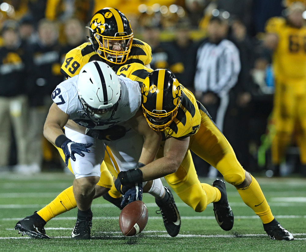 Iowa Hawkeyes linebacker Nick Niemann (49) and linebacker Kristian Welch (34) hit Penn State Nittany Lions tight end Pat Freiermuth (87) and cause him to drop a pass during the second quarter of their game at Kinnick Stadium in Iowa City on Saturday, Oct 12, 2019. (Stephen Mally/hawkeyesports.com)