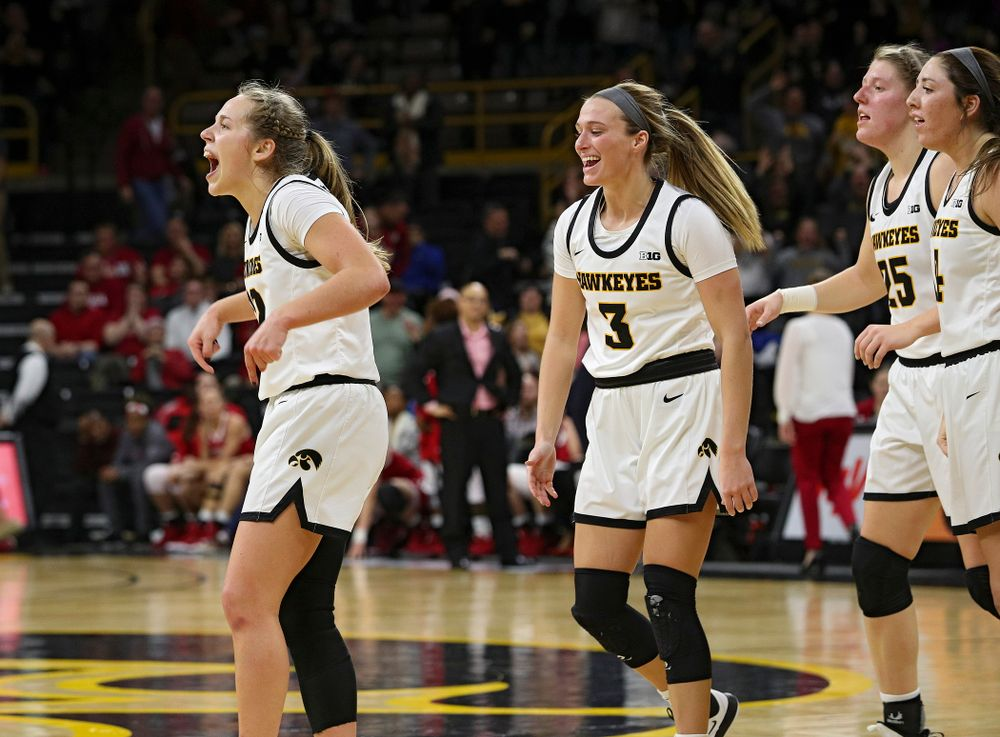 Iowa Hawkeyes guard Kathleen Doyle (22) celebrates with guard Makenzie Meyer (3), forward Monika Czinano (25), and guard Mckenna Warnock (14),  after making a basket while being fouled during the fourth quarter of their game at Carver-Hawkeye Arena in Iowa City on Sunday, January 12, 2020. (Stephen Mally/hawkeyesports.com)