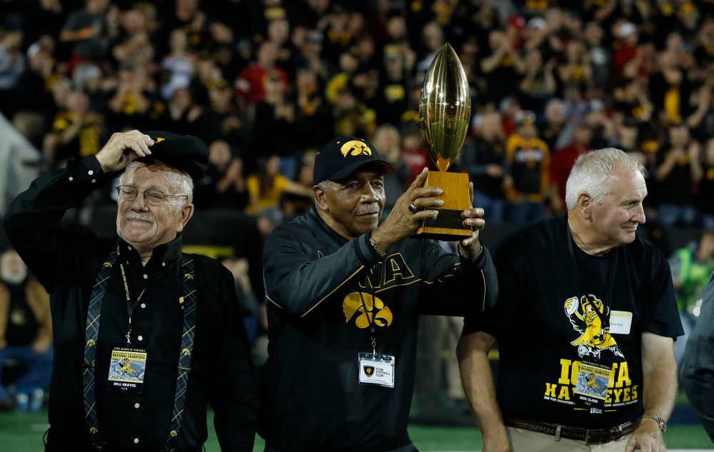 Willie Flemming hols up the  19058 National Championship  trophy as the team is introduced during  the Iowa Hawkeyes game against the Wisconsin Badgers Saturday, September 22, 2018 at Kinnick Stadium. (Brian Ray/hawkeyesports.com)