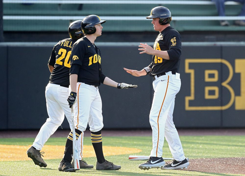 Iowa first baseman Peyton Williams (45) celebrates with infielder Izaya Fullard (20) and designated hitter Trenton Wallace (38) after scoring a run during the third inning of their college baseball game at Duane Banks Field in Iowa City on Tuesday, March 10, 2020. (Stephen Mally/hawkeyesports.com)