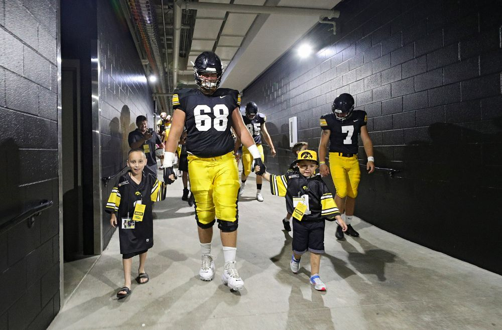Kid Captains Skylar Hardee (left) and Jeg Weets (right) walk with Iowa Hawkeyes offensive lineman Landan Paulsen (68) down the tunnel during Kids Day at Kinnick Stadium in Iowa City on Saturday, Aug 10, 2019. (Stephen Mally/hawkeyesports.com)