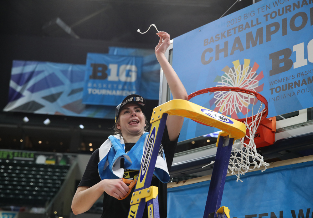 Iowa Hawkeyes forward Hannah Stewart (21) cuts down the net as they celebrate their victory over the Maryland Terrapins in the Big Ten Championship Game Sunday, March 10, 2019 at Bankers Life Fieldhouse in Indianapolis, Ind. (Brian Ray/hawkeyesports.com)