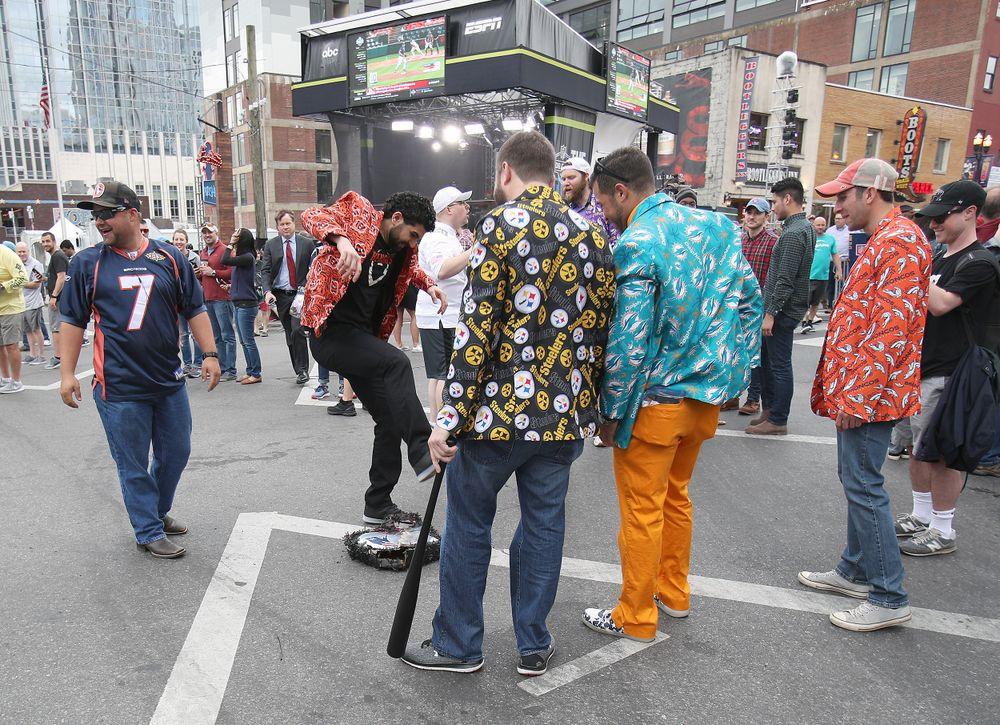Fans of various NFL teams take turns smashing a Patriots pinate