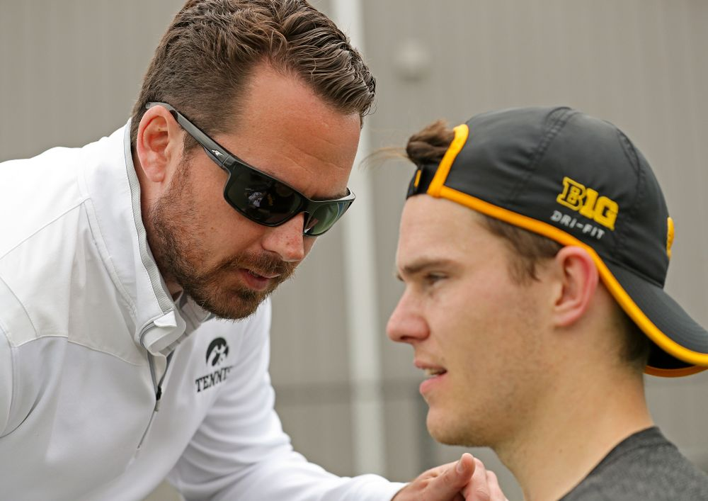 Iowa head coach Ross Wilson (from left) talks with Jonas Larsen during a match against Ohio State at the Hawkeye Tennis and Recreation Complex in Iowa City on Sunday, Apr. 7, 2019. (Stephen Mally/hawkeyesports.com)