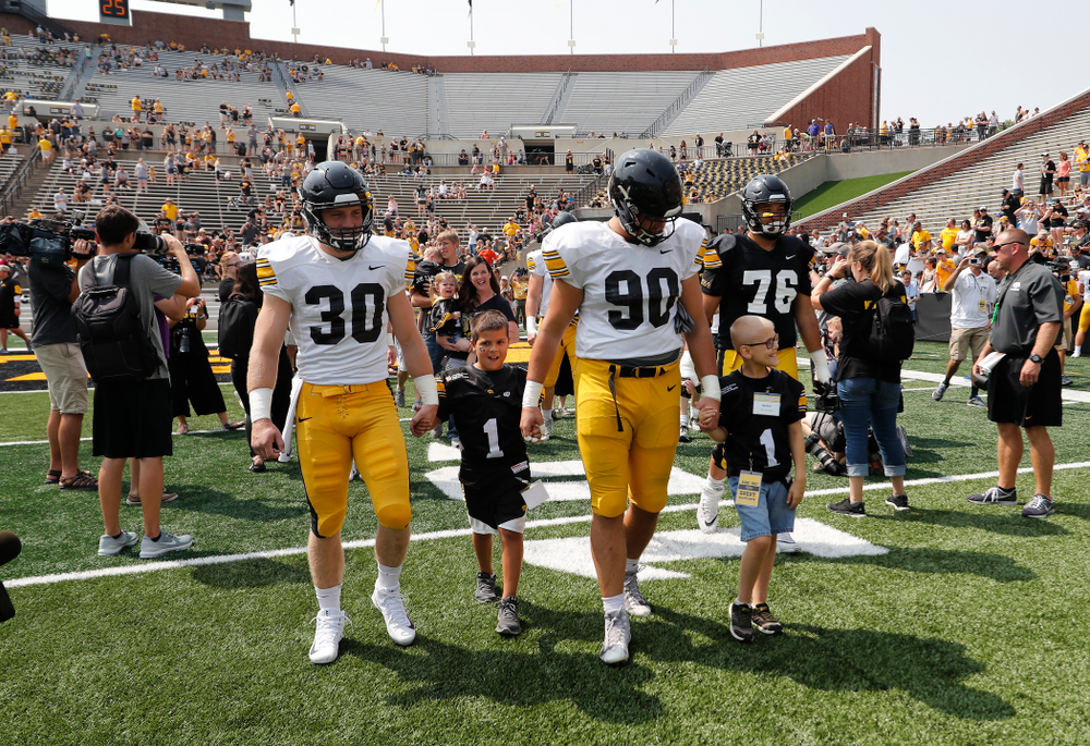 Iowa Hawkeyes defensive back Jake Gervase (30) and defensive end Sam Brincks (90) swarm with the Kid Captains during Kids Day Saturday, August 11, 2018 at Kinnick Stadium. (Brian Ray/hawkeyesports.com)