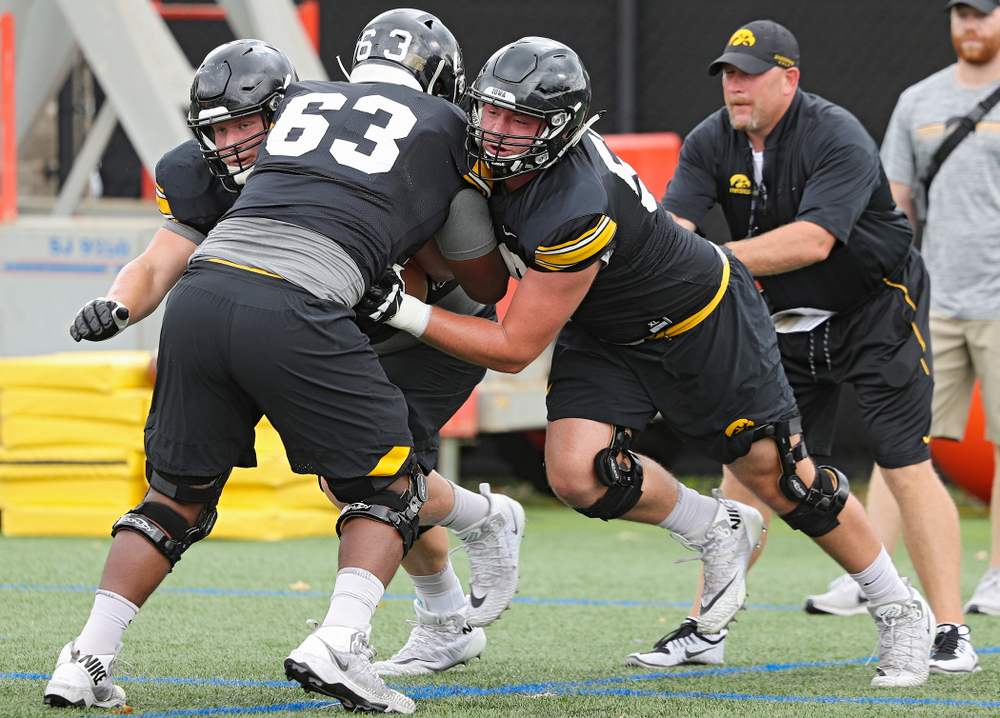 Iowa Hawkeyes offensive lineman Nick DeJong (left) and offensive lineman Ezra Miller (right) block offensive lineman Justin Britt (center) as they run a drill with offensive line coach Tim Polasek  during Fall Camp Practice No. 15 at the Hansen Football Performance Center in Iowa City on Monday, Aug 19, 2019. (Stephen Mally/hawkeyesports.com)