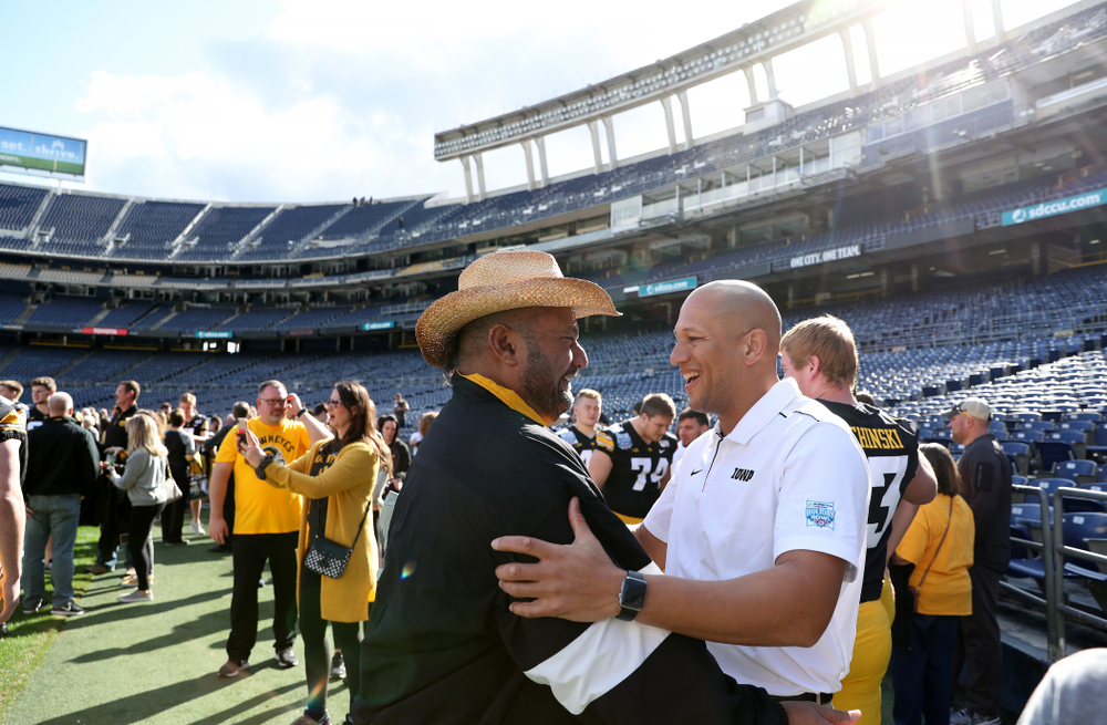 Iowa Hawkeyes special teams coordinator LeVar Woods  hugs Eppy Epenesa following the team photo Wednesday, December 25, 2019 at SDCCU Stadium in San Diego. (Brian Ray/hawkeyesports.com)