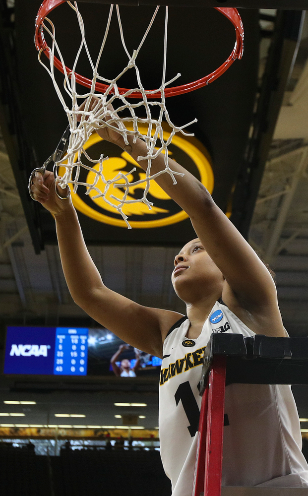Iowa Hawkeyes guard Tania Davis (11) cuts down the net after winning their second round game in the 2019 NCAA Women's Basketball Tournament at Carver Hawkeye Arena in Iowa City on Sunday, Mar. 24, 2019. (Stephen Mally for hawkeyesports.com)