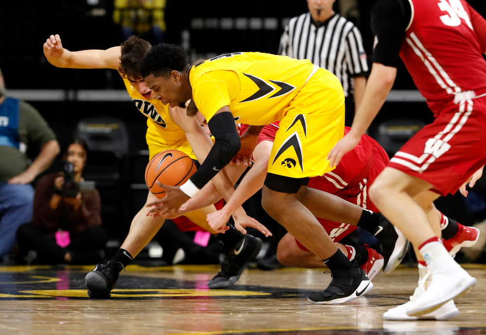 Iowa Hawkeyes guard Isaiah Moss (4) and forward Luka Garza (55)