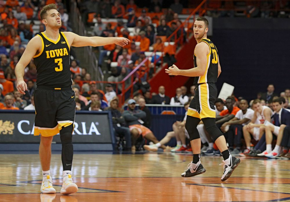Iowa Hawkeyes guard Connor McCaffery (30) holds up three fingers after making a 3-pointer while guard Jordan Bohannon (3) directs his teammates on defense during the second half of their ACC/Big Ten Challenge game at the Carrier Dome in Syracuse, N.Y. on Tuesday, Dec 3, 2019. (Stephen Mally/hawkeyesports.com)
