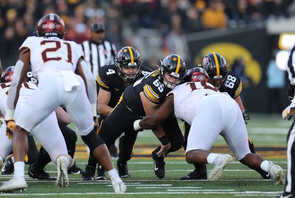 Iowa Hawkeyes offensive lineman Tyler Linderbaum (65) and offensive lineman Landan Paulsen (68) block for quarterback Nate Stanley (4) as he picks up a first down against the Minnesota Golden Gophers Saturday, November 16, 2019 at Kinnick Stadium. (Brian Ray/hawkeyesports.com)