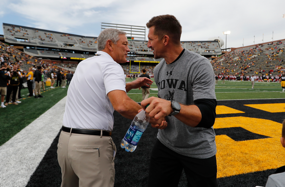 Iowa Hawkeyes head coach Kirk Ferentz  shakes hands with Dallas Clark before their game against the Iowa State Cyclones Saturday, September 8, 2018 at Kinnick Stadium. (Brian Ray/hawkeyesports.com)