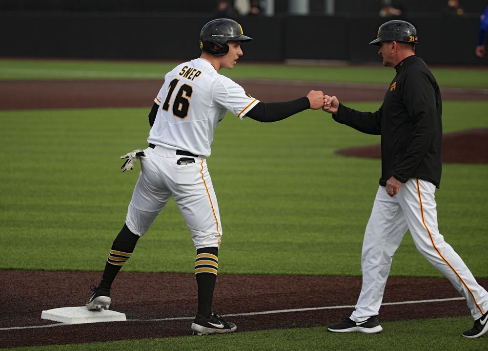 Iowa catcher Tyler Snep (16) gets a first bump from head coach Rick Heller after advancing to third on a wild pitch during the seventh inning of their college baseball game at Duane Banks Field in Iowa City on Wednesday, March 11, 2020. (Stephen Mally/hawkeyesports.com)