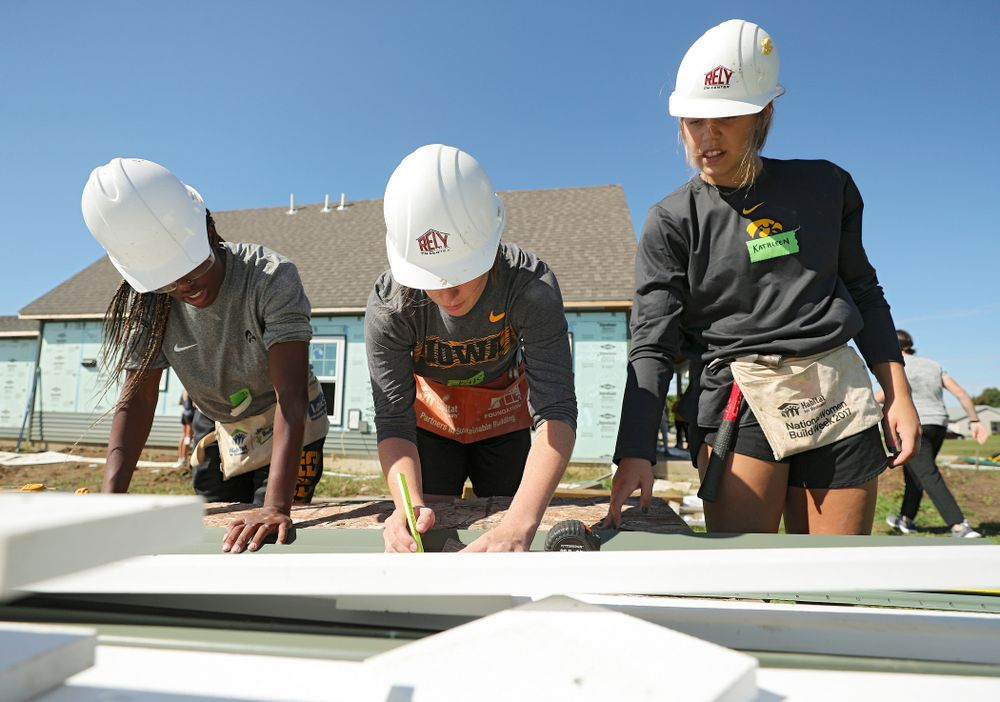 Iowa's Tomi Taiwo (from left), Kate Martin, and Kathleen Doyle work on cutting a piece of siding as they work on a Habitat for Humanity Women Build project in Iowa City on Wednesday, Sep 25, 2019. (Stephen Mally/hawkeyesports.com)