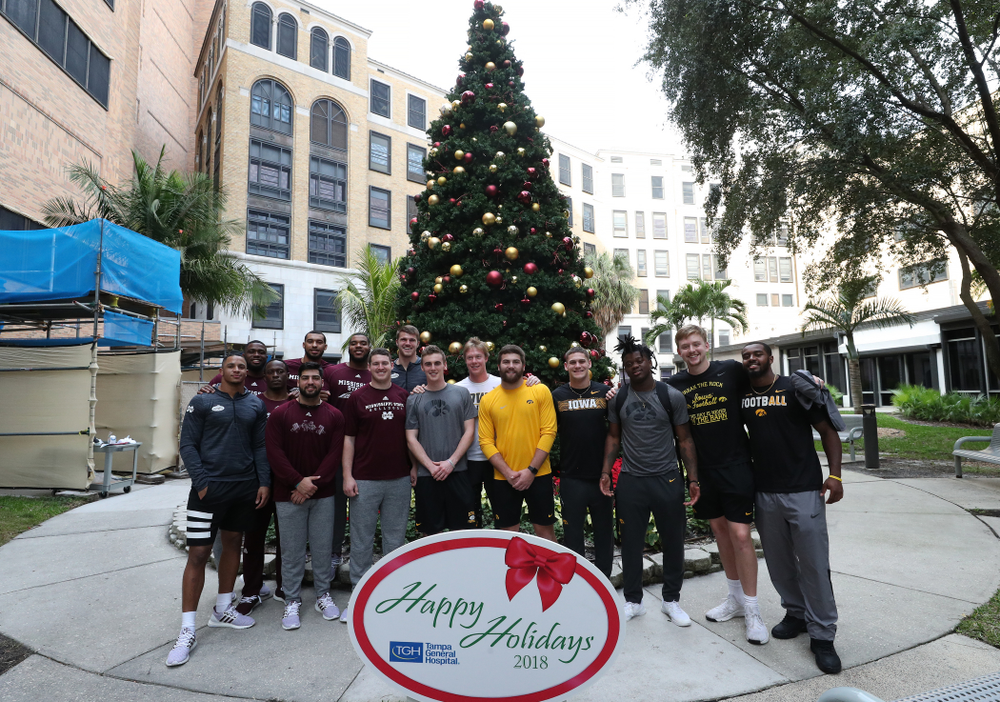Iowa Hawkeyes tight end Ben Subbert (81), punter Ryan Gersonde (2), wide receiver Max Cooper (19), wide receiver Blair Brooks (83), quarterback Spencer Petras (7), linebacker Jayden McDonald (25), and defensive back Dallas Craddieth (15) pose for a photo with players from Mississippi State during a visit to Tampa General Hospital as part of the Outback Bowl Friday, December 28, 2018 in Tampa, FL.(Brian Ray/hawkeyesports.com)