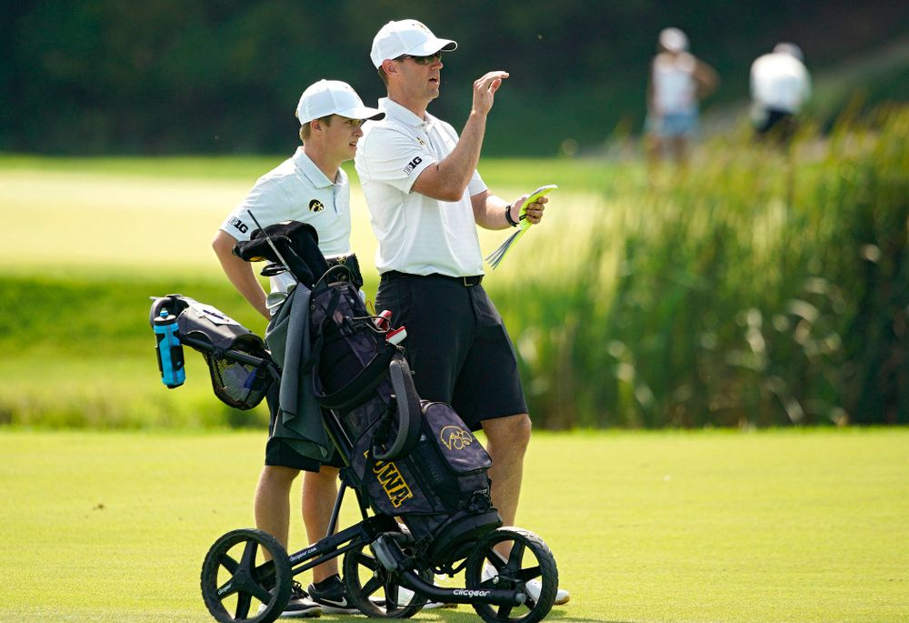 Iowa's Matthew Garside (from left) talks with head coach Tyler Stith on the fairway during the second day of the Golfweek Conference Challenge at the Cedar Rapids Country Club in Cedar Rapids on Monday, Sep 16, 2019. (Stephen Mally/hawkeyesports.com)