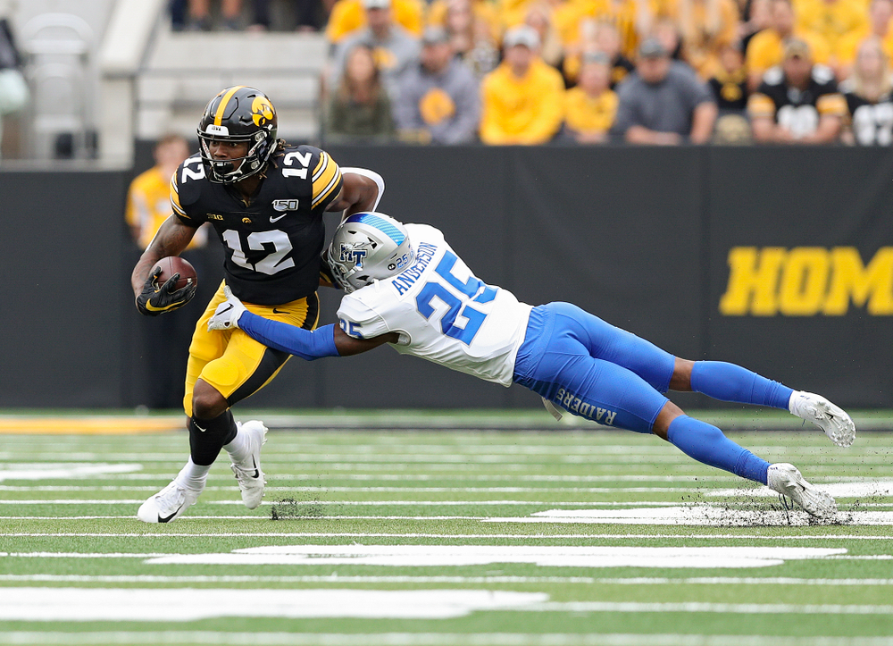Iowa Hawkeyes wide receiver Brandon Smith (12) pulls away from a defender after catching a pass during the first quarter of their game at Kinnick Stadium in Iowa City on Saturday, Sep 28, 2019. (Stephen Mally/hawkeyesports.com)